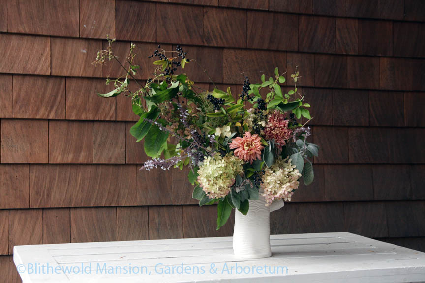 hydrangea, privet, plectranthus, and mums in a fun faux bois vase